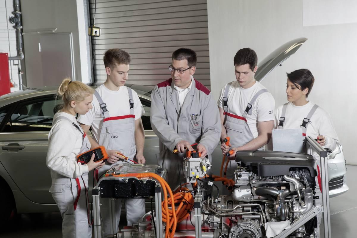 Auszubildende bei Audi an einem Motoren-Modellstück.