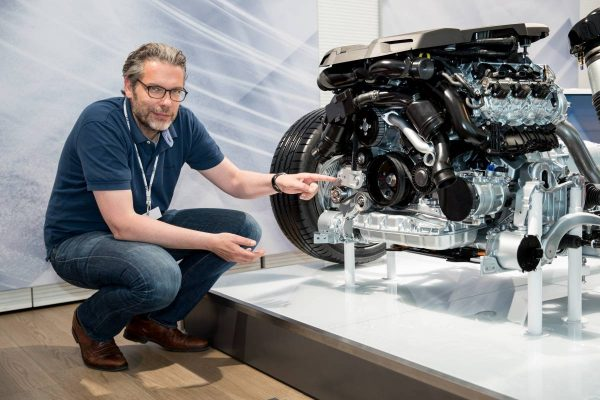 Blog-Autor Tom Schwede vor einem Erklär-Modell für Antriebstechnologien.