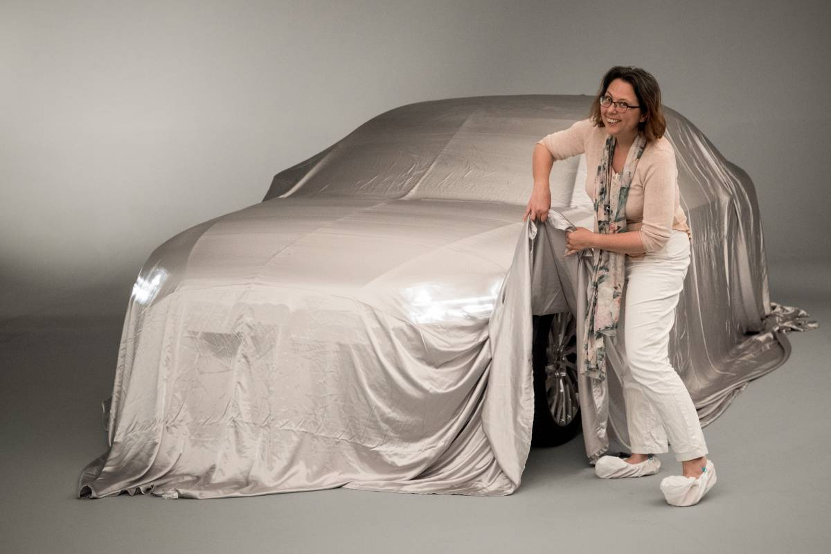 Sandra Schink hebt das Enthüllungstuch am neuen Audi A8 an