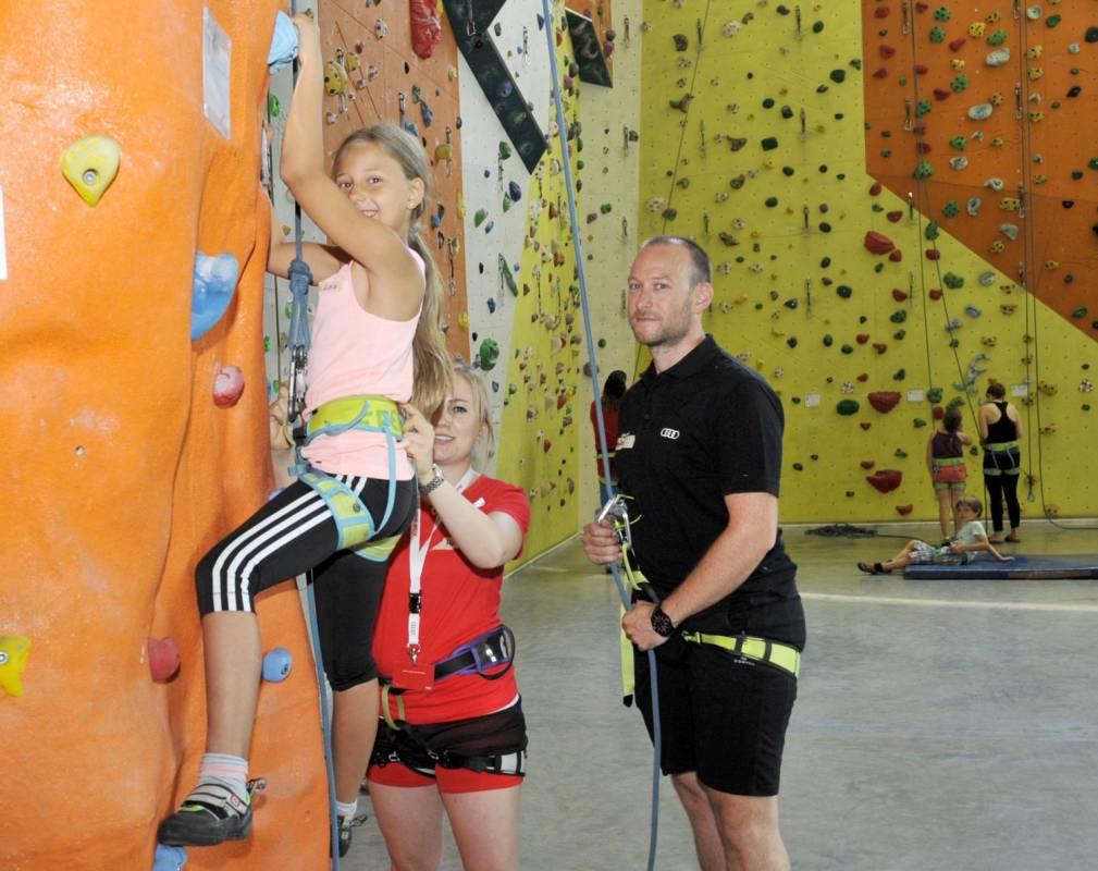 Die neunjährige Lea klettert an einer Kletterwand.
