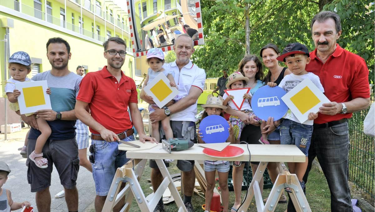 Audianer zeigen Engagement und basteln gemeinsam mit Kindern Straßenschilder.
