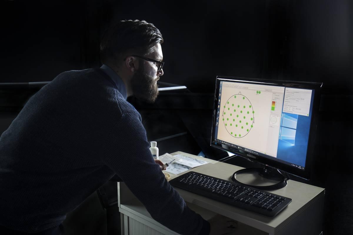 Neurowissenschaftler Mathias Vukelic verfolgt das Experiment am Monitor.