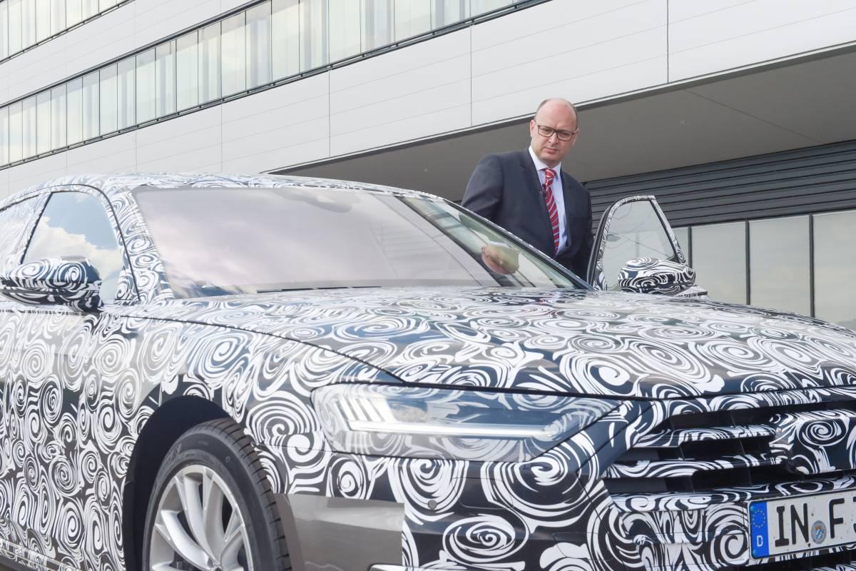 Chauffeur Sinclair steigt in den neuen Audi A8 ein.